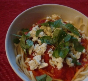Pasta with homemade sauce, feta cheese and fresh basil leaves