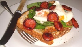 Sauteed chorizo sausage and poached eggs on toast with spinach