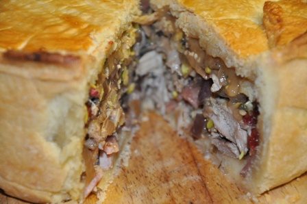 Turkey and bacon pie with a slice removed