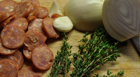 An image of chopped chorizo, onion and thyme