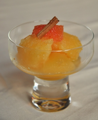 An image of orange sorbet with a cinnamon stick.