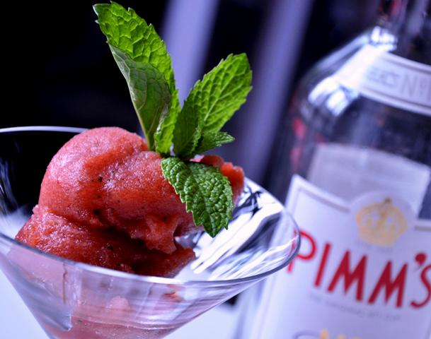 An image of Pimms sorbet in a martini glass with Pimms bottle