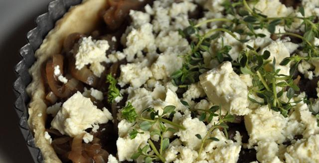 A close up image of onion and feta tart.