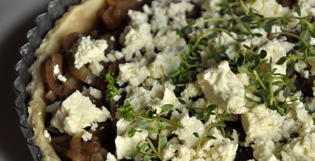 A close up image of onion and feta tart.