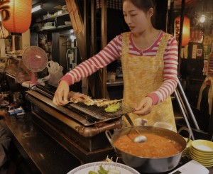 An image of a lady cooking on a Yakitori grill in Japan