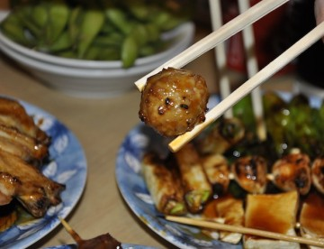 AN image of Yakitori meatballs in a chopstick.