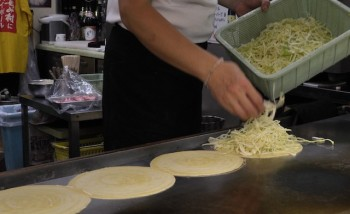 An image of a chef adding shredded cabbage for Okonomiyake filling.