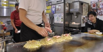 An image of bacon being added to Okonomiyake cooking on a hotplate