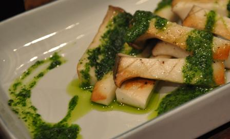 An image of Eringi mushrooms, garlic, Italian parsley in a white dish.