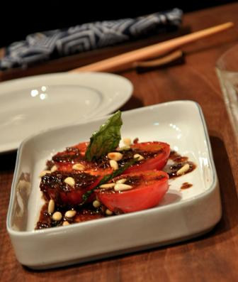 An image of grilled fruit tomato, basil, olive oil.