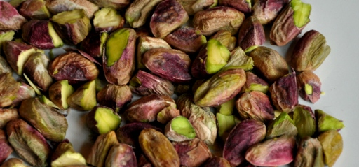 An image of raw pistachio nuts on a plate.