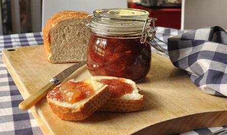An image of bread and jam on a chopping board