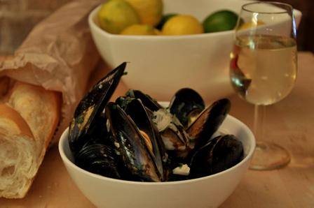 An image of moules mariniere, bread and wine with lemons in a bowl