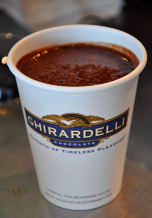 An image of a decadent Ghirardelli hot chocolate in a disposable cup