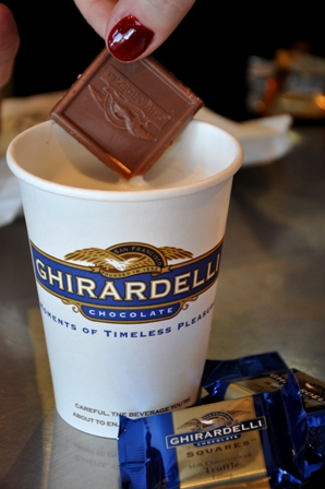 An image of Ghirardelli chocolate squares dipping into hot chocolate in a cup