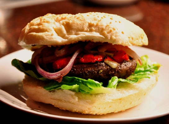 An image of a mushroom burger with charred capiscum and red onion on a white plate