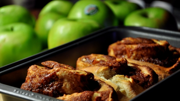 An image of cinnamon and apple rolls with granny smith apples