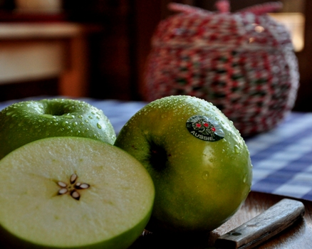 An image of 3 granny smiths apples on a plate