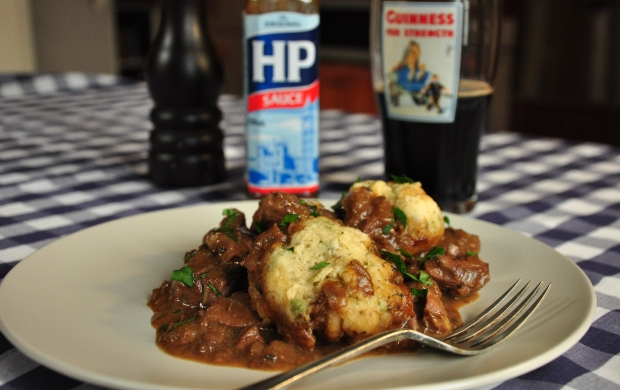 An image of beef stew and dumplings with a pint of Guinness
