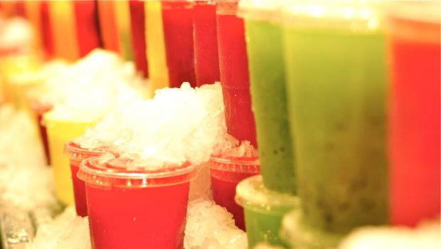 An image of a row of fresh fruit juices in clear cups