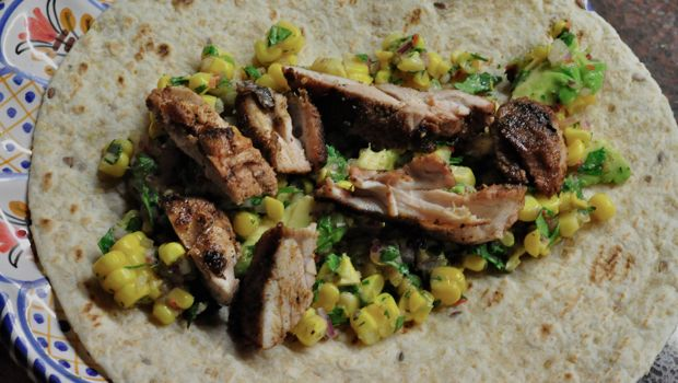 An image of chicken with corn and avocado salsa on a tortilla