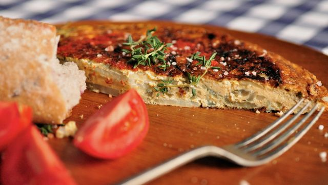 An image of a Spanish tortilla and tomatoes