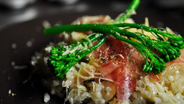 A close up image of Broccolini risotto and serrano jamon
