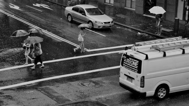 An image of pedestrians crossing a Sydney road in the rain