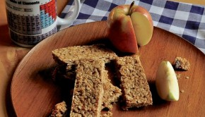 An image of flapjacks and apple on a wooden plate