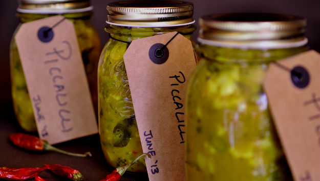 Jars of piccalilli in a row with chilli