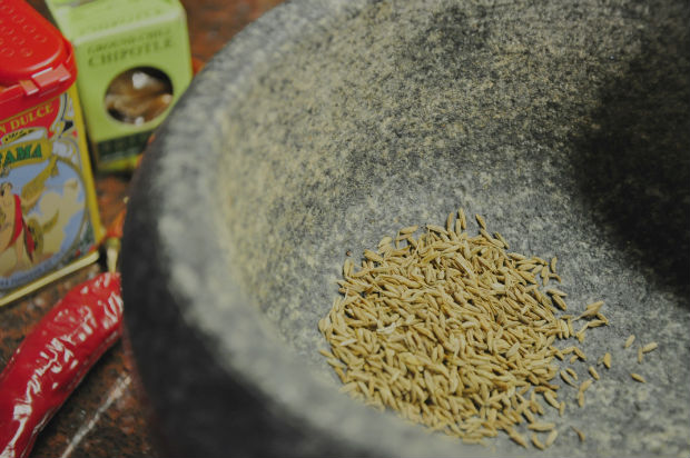 An image of cumin seeds in a pestle