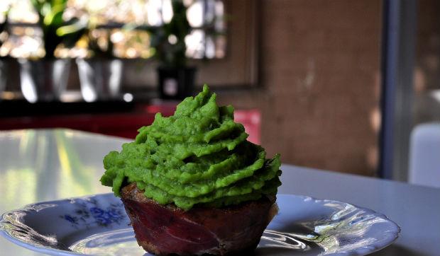 Savoury pork cupcake on a plate next to a window