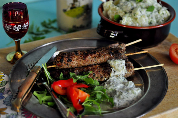 An image of spiced beef koftas on a metal plate with salad