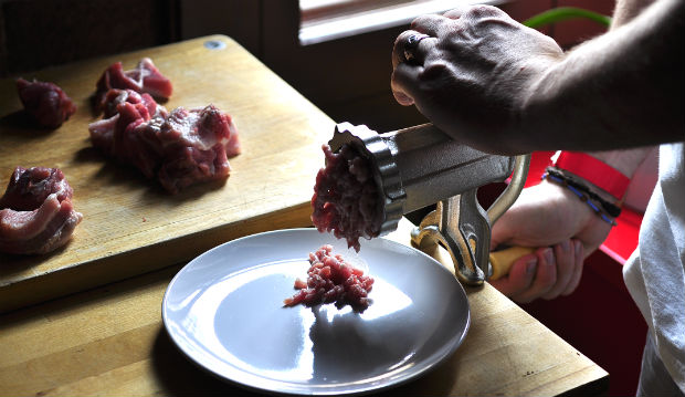 Grinding pork belly with a meat grinder