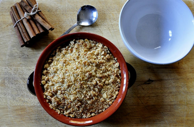Sweet potato, date and apple crumble with a white bowl, spoon and cinnamon
