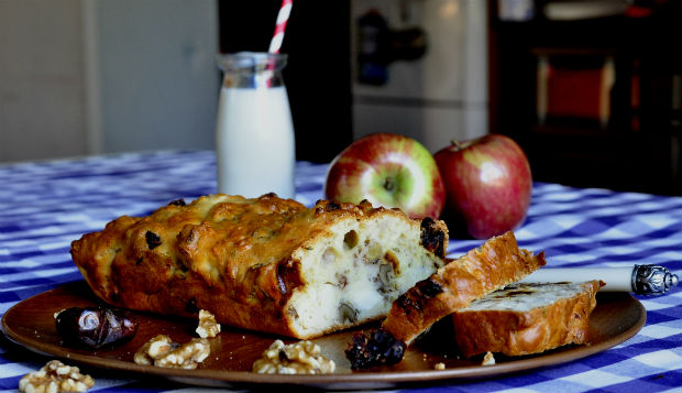 Savoury French cake on wooden plate with apples and milk