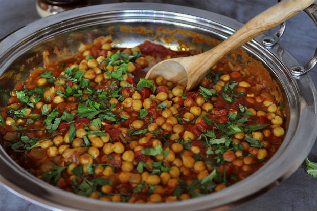 chickpea and sweet potato tagine with wooden spoon and lots of coriander