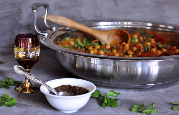 chickpea and sweet potato tagine with wooden spoon and bowl of harissa