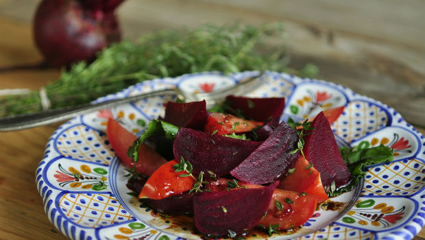 Beetroot and tomato salad on a plate with thyme