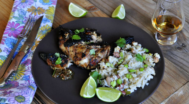 Jerk chicken on a dark plate with lime
