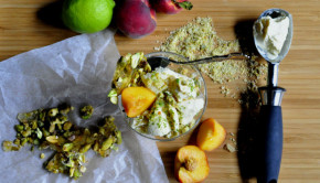Coconut ice cream with pistachio praline and peaches on a board