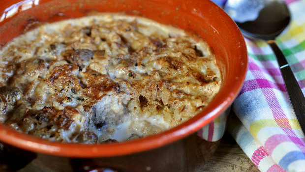 Baked rice pudding with cinnamon in earthenware bowl