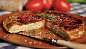 An image of a sliced Spanish tortilla with tomatoes