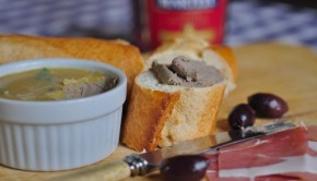 An image of chicken liver pate with bread and olives