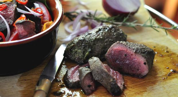 Anti-oxidant salad with freshly cooked kangaroo steak on a board